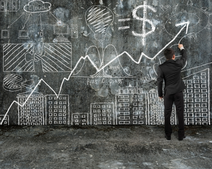 businessman drawing business concept doodles on old concrete wall