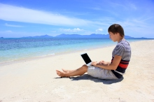 Business man working at a laptop on the beach with azure sea and white sand in Samui, Thailand. He is a freelancer.