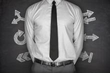 Arrows concept with businessman on black Blackboard