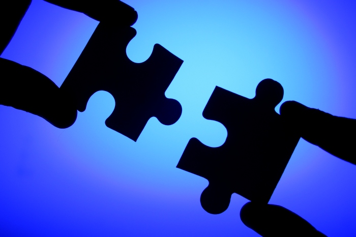 Hands connecting two jigsaw puzzle pieces