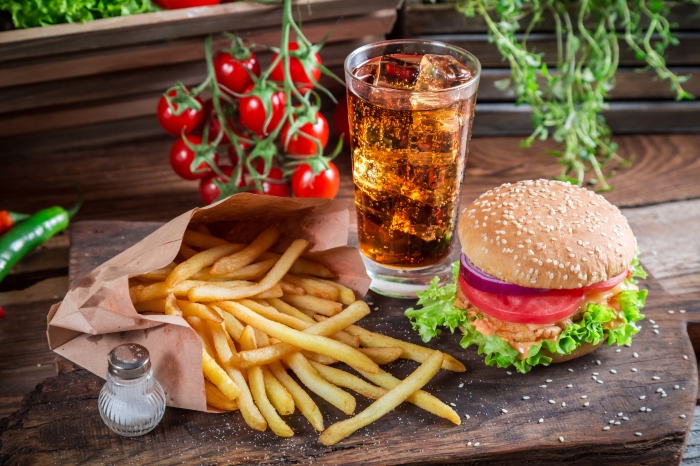 Tasty hamburger with cold drink and fries