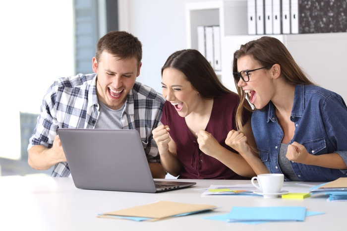 Excited employees reading good news at office