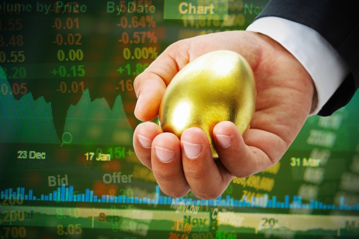 businessman hold golden egg on stock market