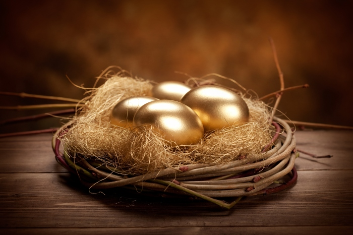 Wooden twigs nest holding four golden eggs