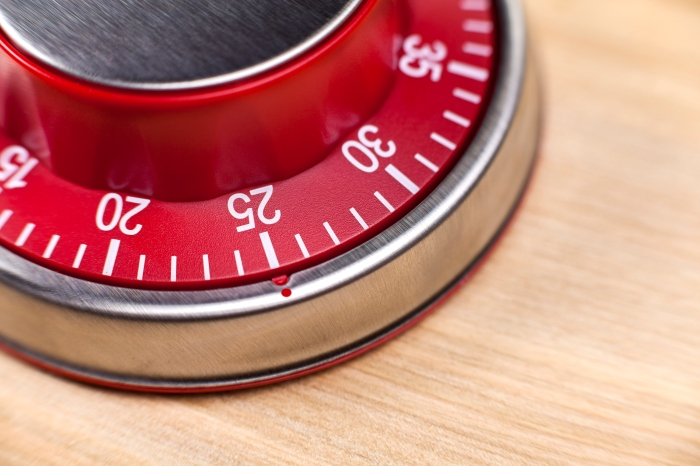 Macro view of a red kitchen timer showing 25 minutes