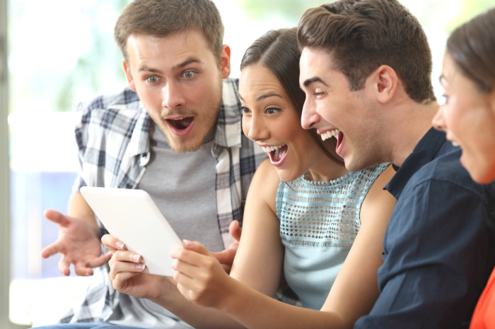 Amazed friends watching media in a tablet